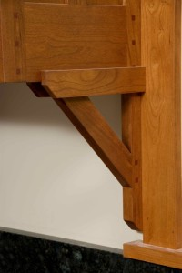 Decorative cherry brackets support cabinets.