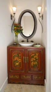 Found objects, like this antique cabinet, bring a stylized and personal touch to the powder room of a traditional Craftsman Bungalow.