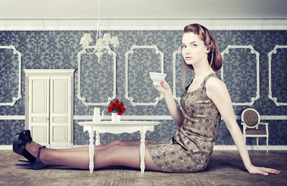woman sitting in room where the furniture is too small